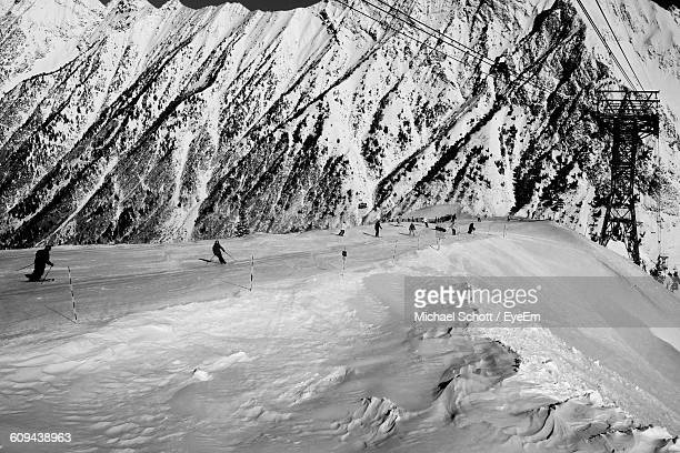 People Skiing On Snow Covered Mountains