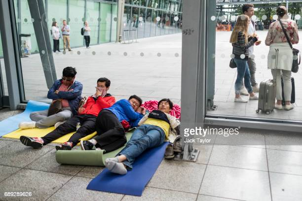 People sleep on mats in Heathrow Airport Terminal 5 on May 28 2017 in London England Thousands of passengers face a second day of travel disruption...