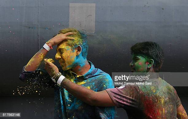 People smile as their face covered in coloured powder during Holi festivals at a temple on March 26 2016 in Kuala Lumpur Malaysia Holi also known as...
