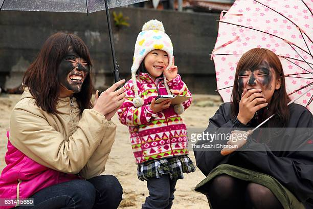 People smile as they are smeared black ink on their faces during the 'Sumitsuke Tondo' ritual on January 8 2017 in Matsue Japan The ritual is a part...