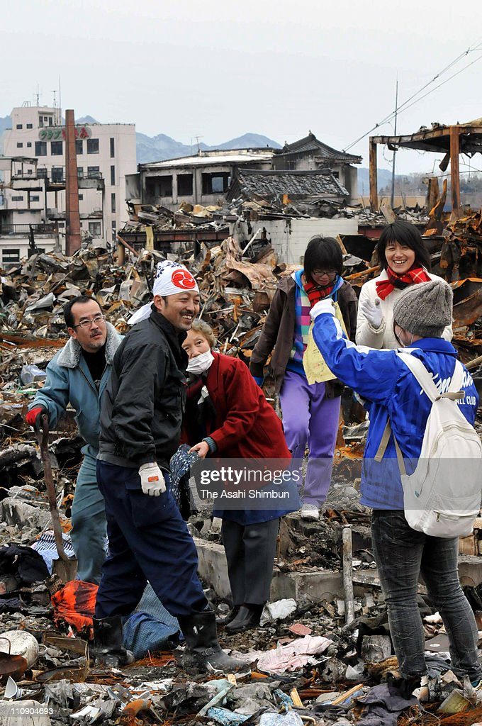 People smile as they find family memorabilia at the place where their house used to stand on March 26, 2011 in Yamada, Iwate, Japan. The 9.0 magnitude strong earthquake struck offshore on March 11 at 2:46pm local time, triggering a tsunami wave of up to ten metres that engulfed large parts of north-eastern Japan, and also damaging the Fukushima nuclear plant and threatening a nuclear catastrophe. The death toll continues to rise with numbers of dead and missing exceeding 20,000 in a tragedy not seen since World War II in Japan.