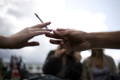 People smoke a joint during a demonstration organised by the CIRC and entitled 'L'appel du 18 juin' to claim for the legalization of the use of...