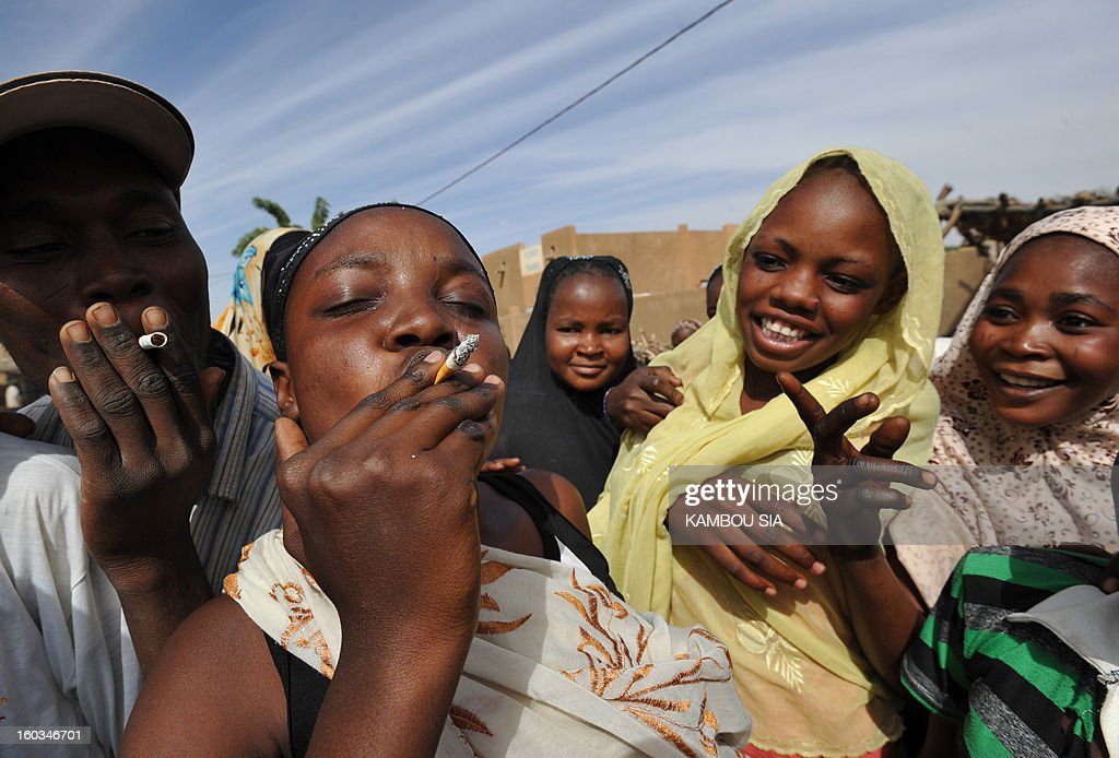 People smoke cigarettes to celebrating the liberation on January 29, 2013 in Ansongo, a town south of the northern Malian city of Gao, as Niger troops entered the city. Troops from Niger and Mali on January 29 entered Ansongo, which along with Gao was recaptured by French-led soldiers over the weekend in a lightning offensive against radicals holding Mali's north. So far, just 2,000 African troops have been sent to Mali or neighboring Niger, many of them from Chad, to boost the French-led offensive which began on January 11 and led to the recapture of several towns, including Ansongo. AFP PHOTO / KAMBOU SIA