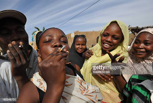 People smoke cigarettes to celebrating the liberation on January 29 2013 in Ansongo a town south of the northern Malian city of Gao as Niger troops...