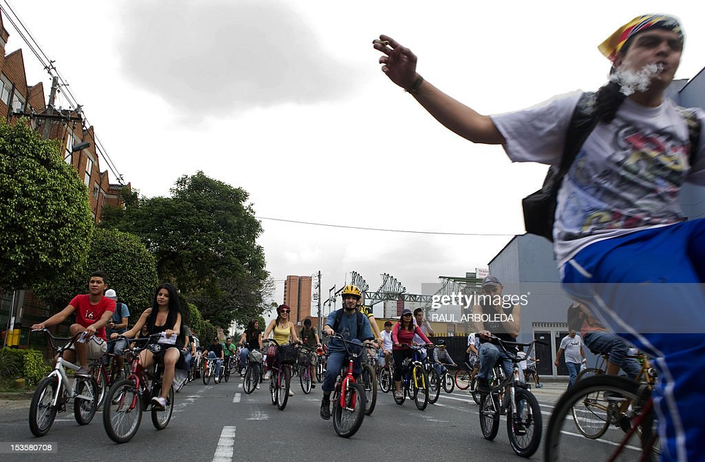 People smoke marijuana as they ride their bikes during the first world bicycle ride against drug trafficking and in favour of the legalization of self-cultivation of marijuana for medicinal and recreational purposes in Medellin, Antioquia department, Colombia on October 6, 2012. AFP PHOTO/Raul ARBOLEDA