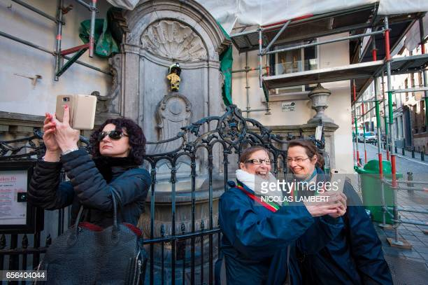 People snap selfies with the 'Manneken Pis' statue wearing a fireman uniform to honour the emergency services and commemorate the victims of last...