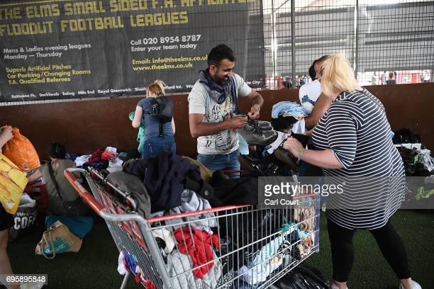 People sort donated products at a fiveaside pitch at Westway sports centre near the burning 24 storey residential Grenfell Tower block in Latimer...