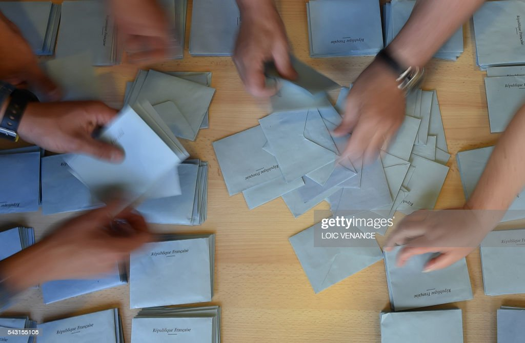 People sort the ballots on June 26, 2016 in Saint-Herblain, outside Nantes, after a local referendum organised in Loire Atlantique regarding the transfer of the Nantes Atlantique airport to Notre-Dame-des-Landes. Nearly one million people living in France's Loire-Atlantique department voted in a referendum which poses the question 'Are you in favour of the project to transfer the Nantes-Atlantique airport to the municipality of Notre-Dame-des-Landes?' to voters. The referendum was organised by the French executive power hoping to find a solution to the issue which has dragged on for 50 years. / AFP / LOIC