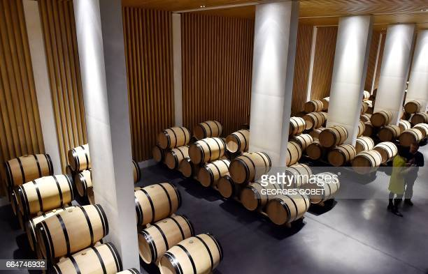 People speak as they stand among wine barrel in the wine cellar of the Chateau Pedesclaux in Pauillac on March 31 2017 Famous architects transform...