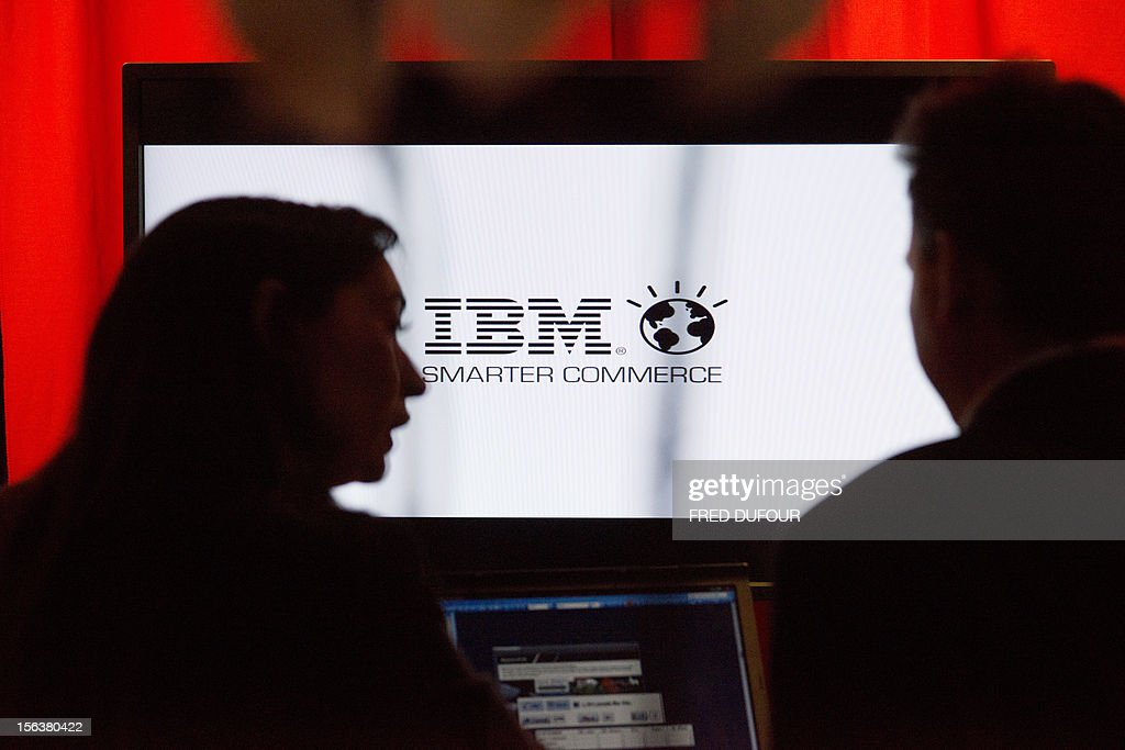 People speaks in front of IBM screen on November 14, 2012 in Paris. AFP PHOTO / FRED DUFOUR