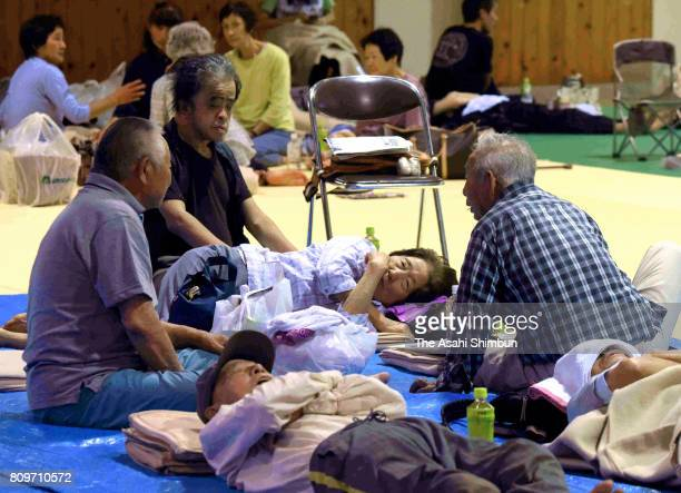 People spend time at a Gymnasium of Haki Junior High School where local residents take shelter as torrential rain hit on July 6 2017 in Asakura...