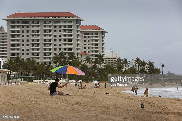 People spend time at the beach on July 1 2015 in San Juan Puerto Rico The island's residents are dealing with increasing economic hardships and a...
