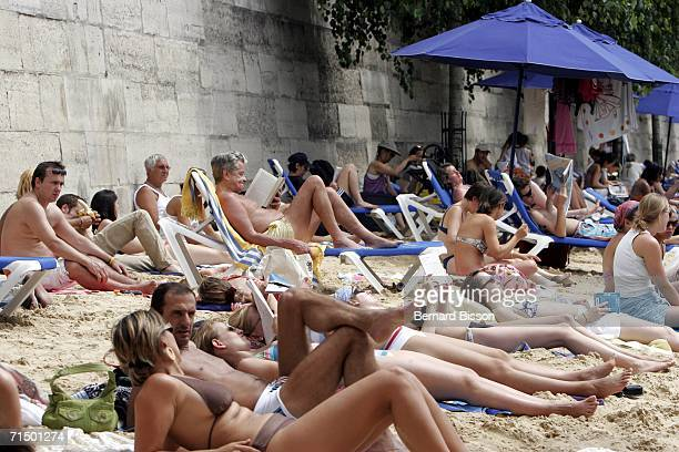 People spend time on the 'Paris Plage' July 22 2006 in Paris France The Paris Plage an artificial beach along the banks of Seine River began in 2002...