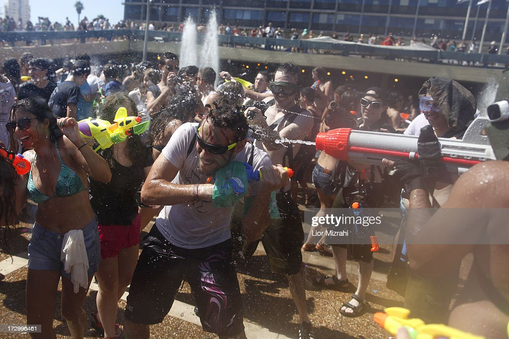 People spray water at each other with a water gun during the annual water fight at Rabin Square July 5, 2013 in Tel Aviv, Israel. Hundreds of Israelis and tourists took part in this ninth annual water fight.