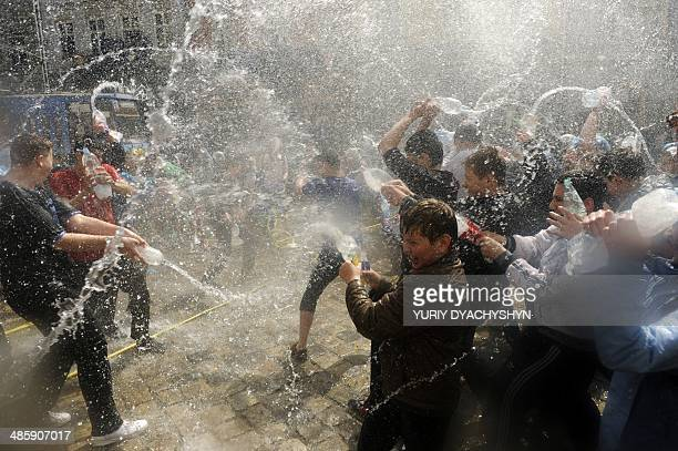 People spray water on one another in the western Ukrainian city of Lviv on April 21 as they celebrate Clean Monday a Ukrainian Christian tradition...