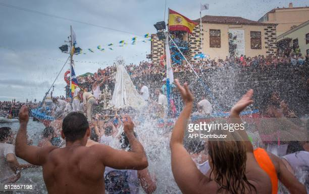 People spread water after carriers of the Great God Power brotherhood have loaded the Virgin del Carmen statue on July 11 2017 at Puerto de la Cruz...