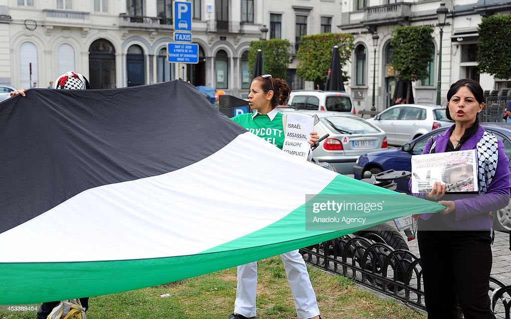 People stage a demonstration with huge Palestinian flag to protest the ongoing Israel's Gaza attacks, in front of European Parliament building, Brussels, Belgium on 9 August, 2014.