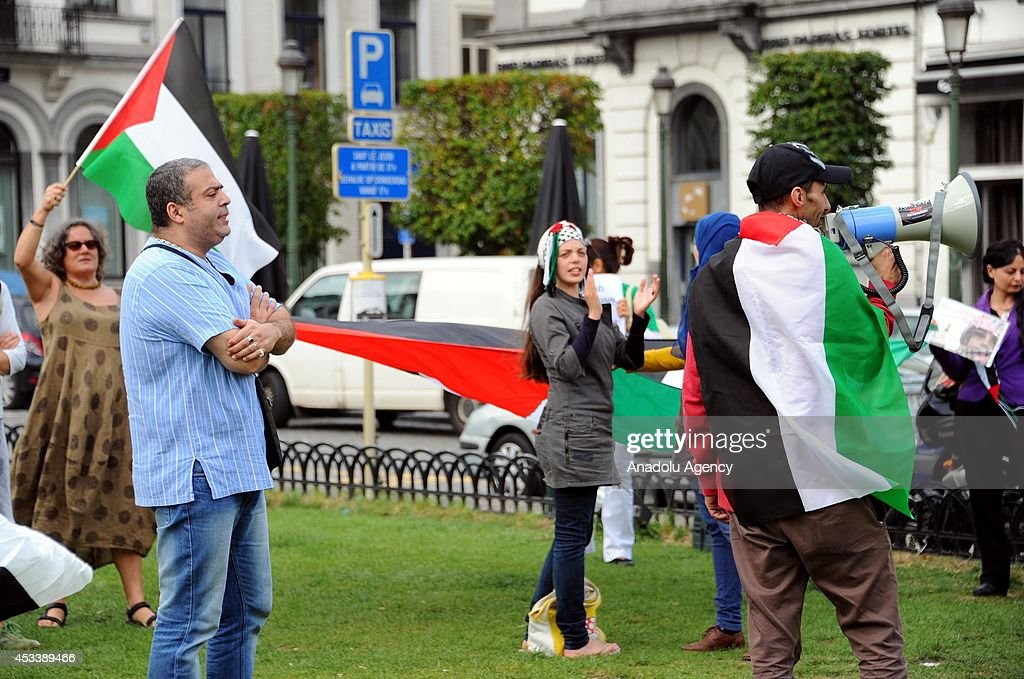 People stage a demonstration with Palestinian flags to protest the ongoing Israel's Gaza attacks, in front of European Parliament building, Brussels, Belgium on 9 August, 2014.