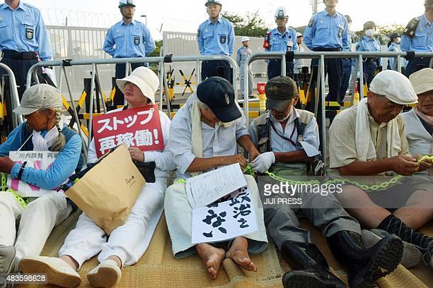 People stage a sitin rally against the restarting of the nuclear reactor outside the gates of the Kyushu Electric Power Sendai nuclear power plant in...