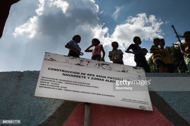 People stand above a government sign informing residents of the construction of a new water system in La Guaira Venezuela on Friday Oct 6 2017 As...