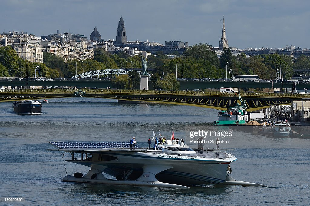 People stand above the Turanor PlanetSolar, the largest solar vessel in the world powered exclusively by the sun, departs to Lorient on September 15, 2013 in Paris, France. The vessel now docked in the River Seine has been gathering data in the Gulf Stream for five months on oceanic processes interacting with the atmosphere.