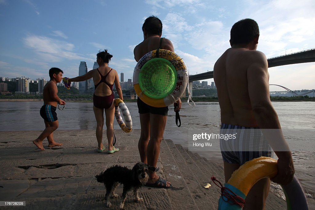 People stand along the bank as they prepare to swim in the Yangtze River on August 4, 2013 in Chongqing, China. Chongqing is a major city in southwest China and became the municipality was created on 14 March 1997. It known as a 'Mountain City' and 'River City' was constructed on the mountain and along the Yangtze River.