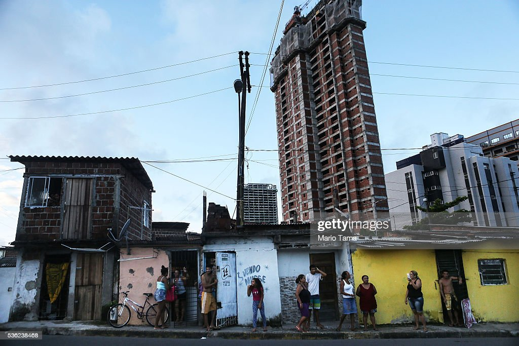 People stand along the Olympic torch route as they await the torchbearer to pass on May 31, 2016 in Recife, Brazil. The Olympic flame will pass through 329 cities from all states from the north to the south of Brazil, before arriving in Rio de Janeiro on August 5, for the lighting of the cauldron for the Rio 2016 Olympic Games. The games will be held amidst an economic and political crisis in the country.