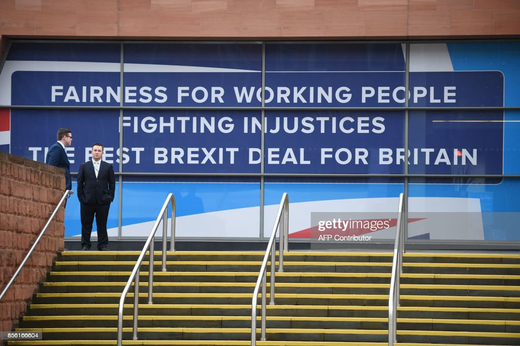 People stand alongside a hoarding with a political message at the Manchester Central convention centre, in Manchester on October 1, 2017, the first day of the Conservative Party annual conference. British Prime Minister Theresa May's Conservative Party gathers on October 1, 2017, for its annual conference, dominated by questions about her leadership and splits on Brexit. / AFP PHOTO / Oli SCARFF
