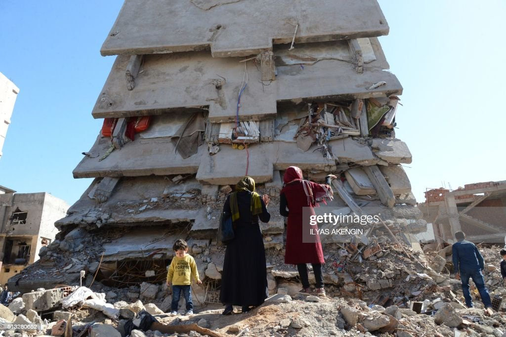 TOPSHOT People stand among the rubble of damaged buildings following heavy fighting between government troops and Kurdish fighters in the Kurdish...