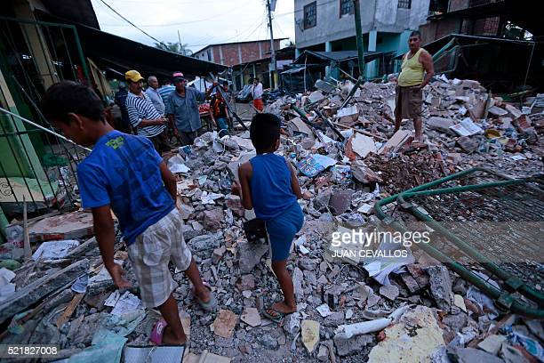 TOPSHOT People stand amongst the rubble of fallen homes in Manta on April 17 after a powerful 78magnitude earthquake struck Ecuador on April 16 At...