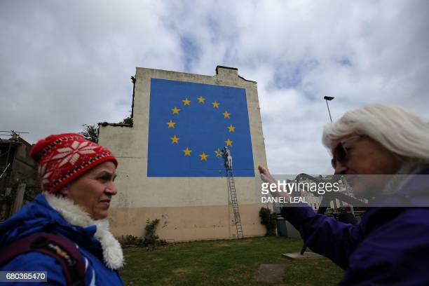 People stand and look at recently painted mural by British graffiti artist Banksy depicting a workman chipping away at one of the stars on a European...