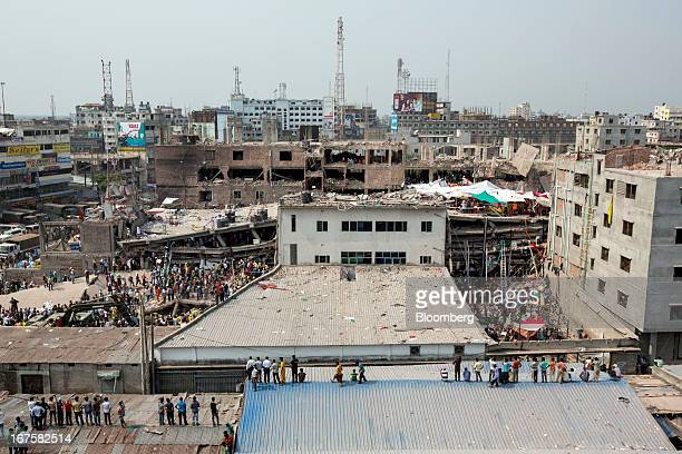 People stand and watch as rescue workers search for victims amongst the debris of the collapsed Rana Plaza building in Dhaka Bangladesh on Friday...