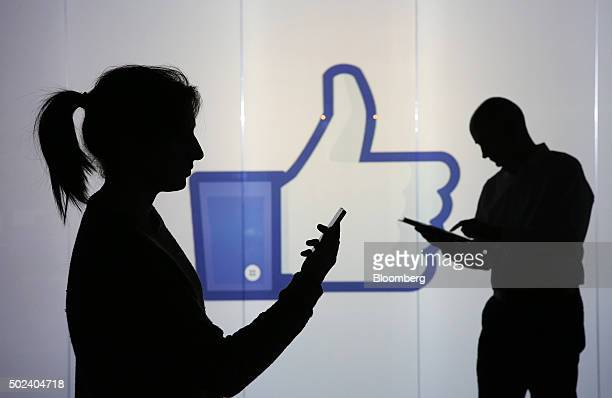 People stand and work on mobile devices a smartphone left and a Apple Inc iPad whilst framed against a wall bearing Facebook Incs 'Thumbs Up' symbol...