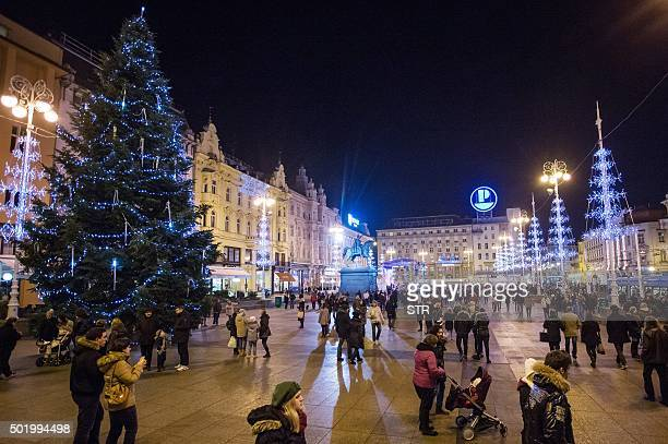 BRIEN People stand around a christmas tree on Ban Jelacic Square in central Zagreb on December 13 2015 With an ice sculpture festival brass band...