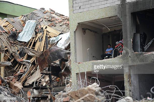 People stand around a damaged building as officers work in debris on May 15 2013 at Reyhanli in Hatay just a few kilometres from the main border...