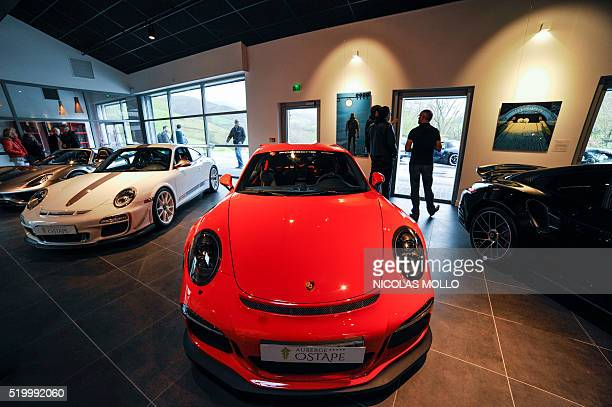 People stand around Porsche cars on April 9 2016 during the inauguration of a private museum dedicated to Porsch at the Auberge Ostape in Bidarrau...