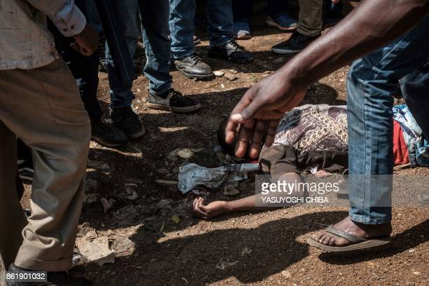 TOPSHOT People stand around the body of Michael Okoth Okello a 18 years old man who was allegedly shot by a police officer while he was buying sorbet...