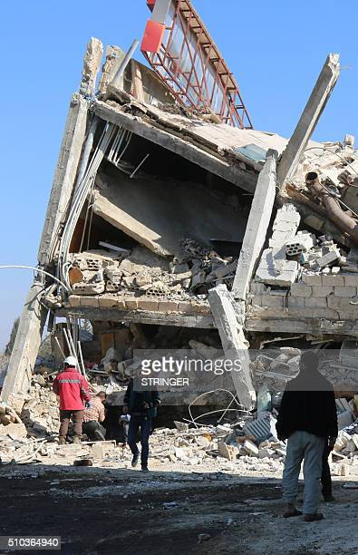 People stand around the rubble of a hospital supported by Doctors Without Borders near Maaret alNuman in Syria's northern province of Idlib on...
