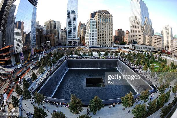 People stand around the South Pool of the 9/11 Memorial during the tenth anniversary ceremonies of the September 11 2001 terrorist attacks at the...
