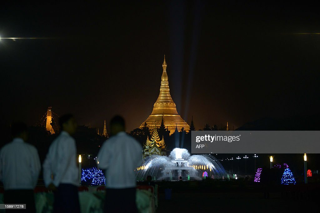 People stand as they attend a flag-raising ceremony to mark Myanmar's 65th Independence Day at the People's Square near Shwedagon pagoda (C back) in Yangon January 4, 2013. Myanmar, formerly known as Burma, gained independence from Britain on January 4, 1948. AFP PHOTO / YE AUNG THU