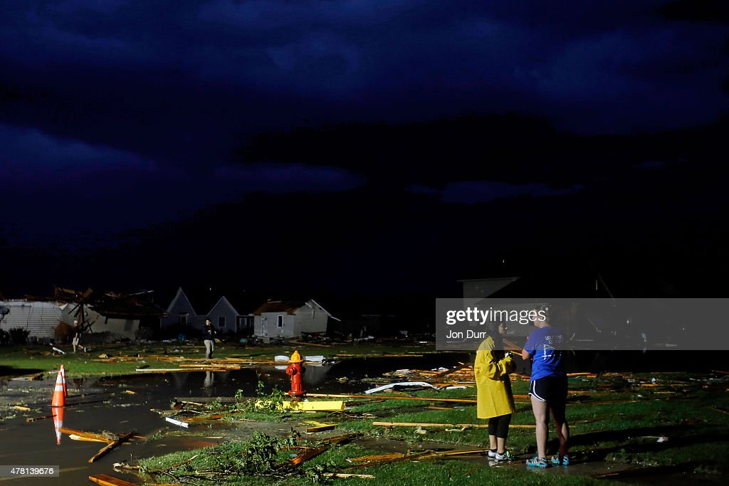 People stand as they look at the damage caused by a tornado while storms continue thourghout the area on June 22 2015 in Coal City Illinois