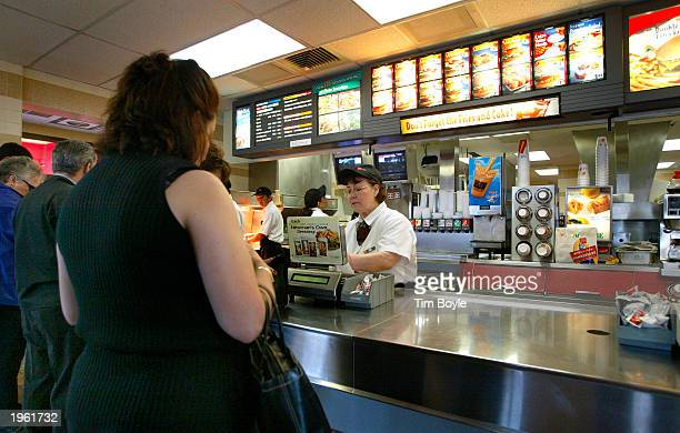 People stand at a counter inside a McDonald's fast food restaurant April 30 2003 in Niles Illinois McDonald's Corporation announced that results for...