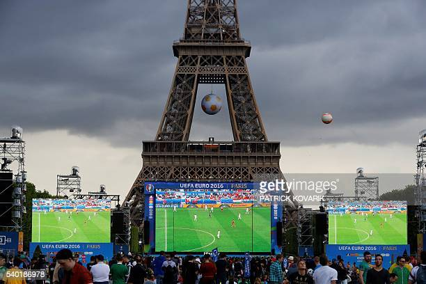 TOPSHOT People stand at a fan zone near the Eiffel Tower in Paris on June 14 2016 during an Euro 2016 football tournament match / AFP / PATRICK...