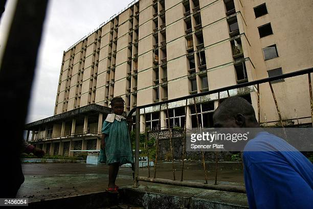 People stand at the entrance to the former Ducor Palace Hotel September 2 2003 in Monrovia Liberia The Ducor which closed when fighting began in 1990...