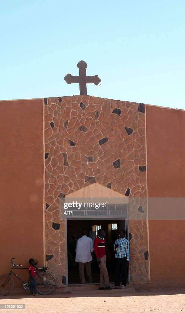 People stand at the entrance to the St. Bakhita's parish church in the Jaborona settlement for displaced people from South Kordofan and South Sudan in the desert near Khartoum's twin city Omdurman on December 23, 2012. From their homes made of mud brick, or from roughly-built shelters, Sudan's displaced will gather on the sandy lot of St. Bakhita's parish church for Christmas mass. AFP PHOTO/IAN TIMBERLAKE