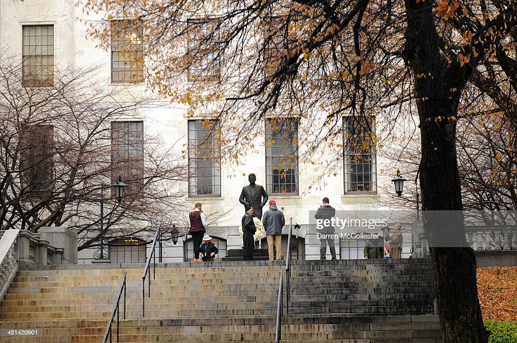 People stand at the John F. Kennedy statue at the State House November 22, 2013 in Boston, Massachusetts. Kennedy, born in Brookline Massachusetts, was killed 50 years ago on this day by Lee Harvey Oswald in Dallas Texas in 1963.