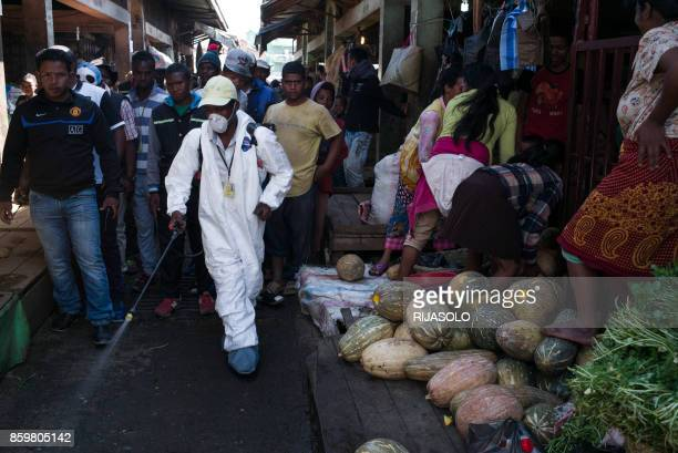 People stand back as a council worker sprays disinfectant during the cleanup of the market of Anosibe in the Anosibe district one of the most...