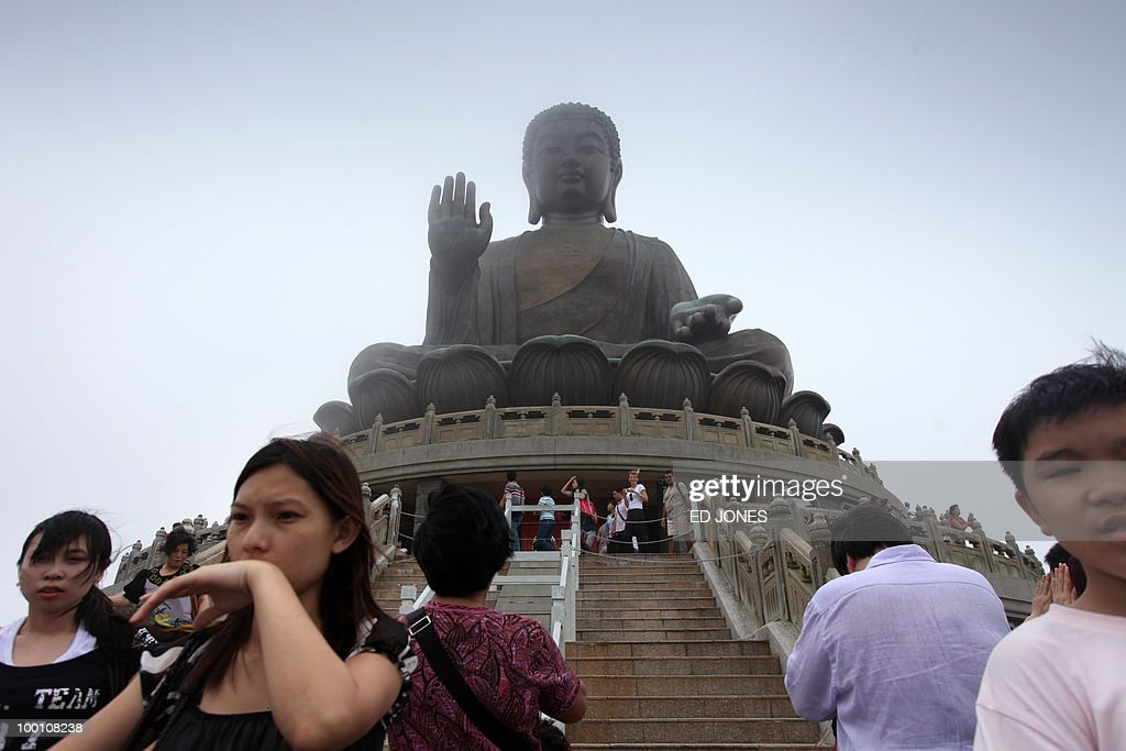 People stand before the Tian Tan Buddha statue, also known as the Big Buddha, on Lantau island in Hong Kong on May 21, 2010. Buddhists throughout Asia are celebrating the birthday of Siddhartha Gautama, the spiritual teacher who founded Buddhism. Hong Kong's Big Buddha statue was until 2007 the tallest of its kind, standing 34 metres (112 feet) tall.