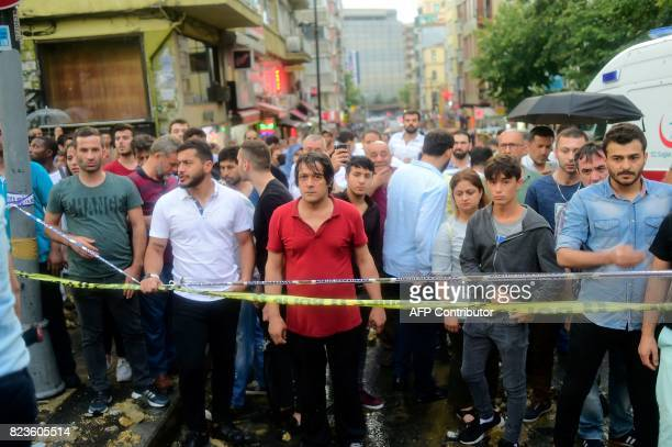 People stand behind a cordon as rescue workers search for people after the wall of a Christian cemetery collapsed in Istanbul on July 27 2017 / AFP...