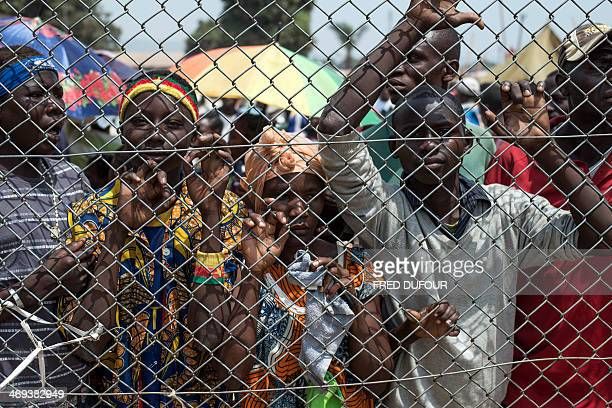 People stand behind a gate at Mpoko Airport in Bangui Central African Republic as food is being unloaded from a cargo aircraft on February 14 2014...